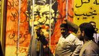 Egyptians pose in front of anti-Egyptian President Mohammed Morsi graffiti