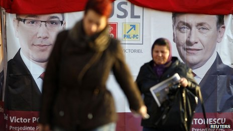 "People walk past an election poster with the pictures of Romania""s Social Liberal Union (USL) leaders, leftist Prime Minister Victor Ponta, the president of Social Democrat Party, and Crin Antonescu, the president of National Liberal Party (R), in downtown Bucharest December 4, 2012."