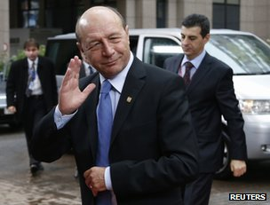 Romanian President Traian Basescu waves as he arrives at an EU summit in Brussels, 23 November