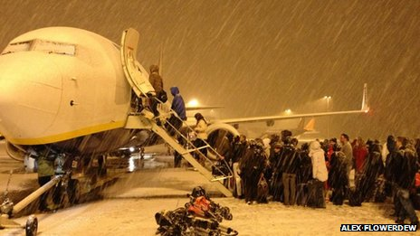 Passengers boarding aircraft in heavy snow