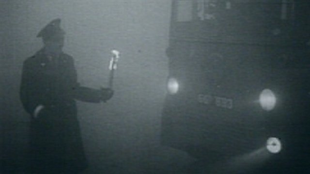 A policeman directs a bus with a flame during the Great Smog