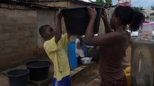 Woman and child carrying a bucket of water in Adjako