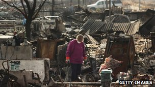 A woman goes through debris where her home used to stand in Breezy Point, New York 4 December 2012