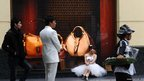 A newly married couple pose outside a Gucci store in Hanoi, Vietnam