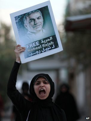 A Bahraini anti-government protester chants slogans as she holds up a pictures of jailed human right activist Nabeel Rajab, 3 December 2012