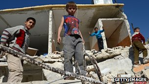 Syrian children play on the rubble of buildings