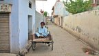 Man sitting on bicycle cart
