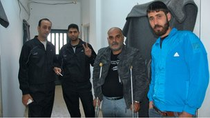 Four residents of Cyber City camp stand in the corridor including Jihad Khalil (with crutches)