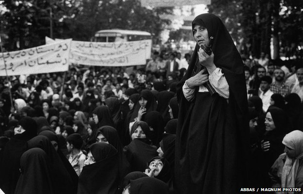 A militia woman armed with an Uzi sub-machine gun controls a demonstration against Iraq, Tehran, 1979
