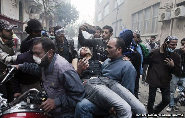 A protester with a wound to the head is evacuated on a motorcycle from clashes in Tahrir Square in Cairo, 22 November 2011