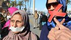 Libyan women wear tape over their mouths during a protest in Tripoli calling for more freedom of expression, greater transparency and a more important role for the judiciary and the security forces (5 December)