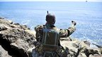 A soldier in Kismayo overlooking the sea, taking a photo of himself - Thursday 29 November 2012