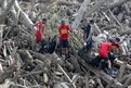 Rescuers carry body bags containing bodies of typhoon victims recovered from the debris in New Bataan town, Compostela Valley, southern Philippines