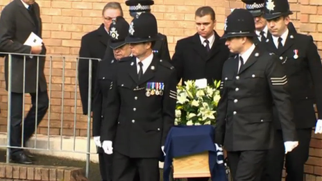 Police officers carrying the coffin at the funeral