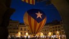 A hot air balloon decorated with the flag that symbolising Catalonia&#039;s independence is seen in the middle of the main square in the town of Vic.