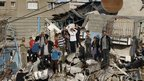 Palestinians stand on the rubble of a house, which witnesses said was destroyed in an Israeli air strike, as they watch the convoy of Hamas leader Khaled Meshaal in Gaza City December 7, 2012