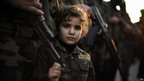 A Palestinian girl dressed as a Ezzedine al-Qassam brigade member during a march by Hamas' armed wing in Beit Hanun on December 6, 2012