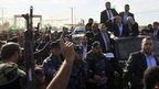 Khaled Meshaal and Ismail Haniya  wave from a vehicle during a parade following Meshaal's arrival in Rafah, southern Gaza on December 7, 2012