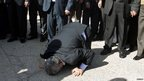 Meshaal prays on the ground as he arrives in Gaza