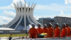 Coffin carried past the Metropolitan Cathedral in Brasilia by fire engine. 6 Dec 2012