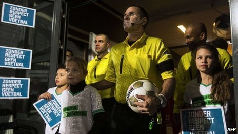"Dutch referees stand next to children holding signs reading ""Without respect, no football"" before a game in Almelo. Photo: 7 December 2012"