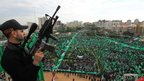 A member of Hamas stands guard during the rally in Gaza, 8 Dec