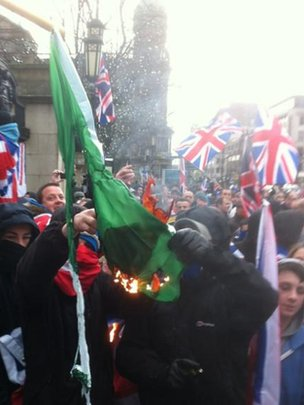 Loyalists set fire to an Irish tricolour outside Belfast City Hall