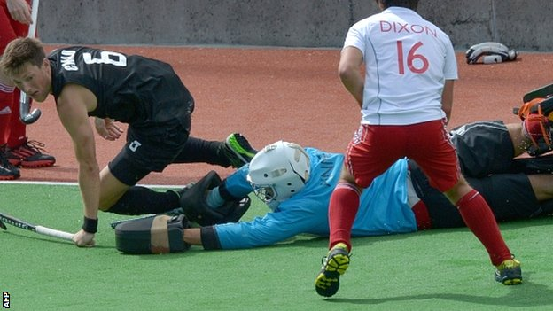 New Zealand's Simon Child tussles with England goalkeeper George Pinner