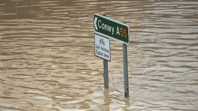 Road sign surrounded by flood water