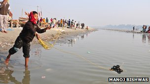 Rohit Kumar, 10, casts his magnets to try and get some coins from the river