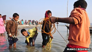 Young boys collecting coins in the river with magnets attached to colourful ropes