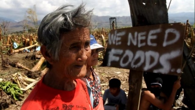"Woman with sign saying ""We need food"""