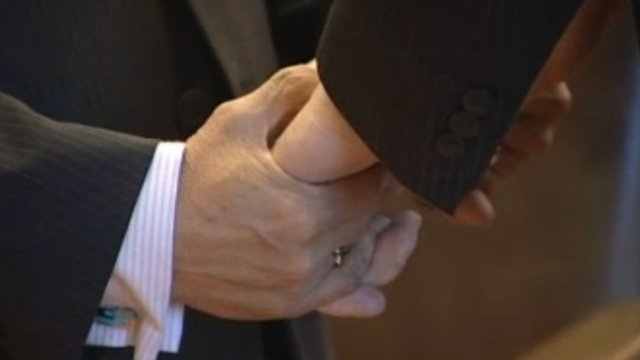 Two men hold hands at a civil ceremony