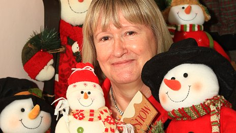 Diana Howes sits on the stairs with part of her collection of snowmen