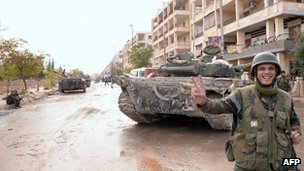A Syrian army soldier flashes the V-sign for victory as he stands close to tanks in Aleppo. Photo: November 2012