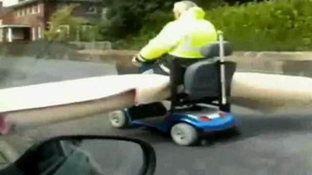 Man with carpet on a mobility scooter