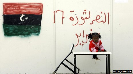 "A young displaced girl from Tawergha perches on top of a table, a sign behind her reads ""Victory for the 17 November protests"""