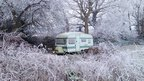 A caravan in a garden is surrounded by frosted trees and branches. The whole scene is white and looks pretty.