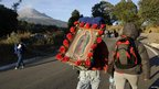 A pilgrim carries a picture of the Virgin of Guadalupe in Paso de Cortes, in the Mexican state of Puebla 9 December 2012