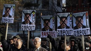 "South Korean protesters shout slogans as they hold the pictures of North Korean leader Kim Jong-un with text saying ""Out Kim Jong-un"" in Seoul, South Korea, 12 December 2012"
