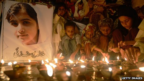 Children light candles and hold a picture of Malala Yousafzai