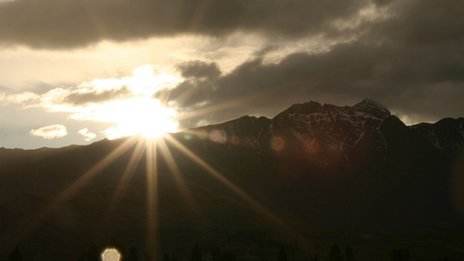 Sun rising over a mountain range