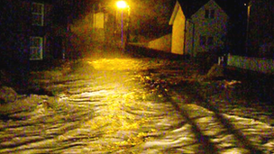 Water pouring through street in Llanfair Talhaiarn during flooding in November 2012