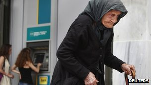 An elderly woman walks past an ATM machine in Athens. Photo: May 2012