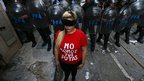 "A demonstrator, wearing a T-shirt that reads in Spanish ""We are not your prostitutes,"" stands in front of police officers in Buenos Aires"