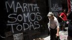 "A woman walks by graffiti that reads in Spanish ""We're all Marita"" written by protesters outside the building used by government representatives of Argentina's Tucuman province in Buenos Aires"