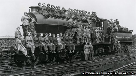 Women locomotive cleaners sitting on an engine, Bradford, West Yorkshire, 23 March 1917