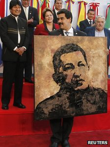 Nicolas Maduro holds a portrait of President Hugo Chavez given to him by Argentina&#039;s President Cristina Fernandez (not pictured) during the annual summit of the Mercosur in June 2012