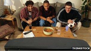 Three men watch TV