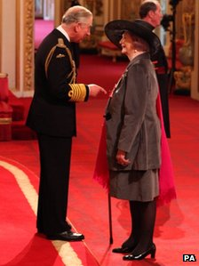 April Ashley receiving her MBE medal from Prince Charles